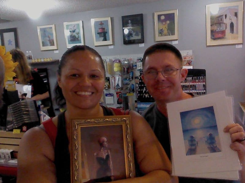 happy couple holding Madame X-Ray and some prints