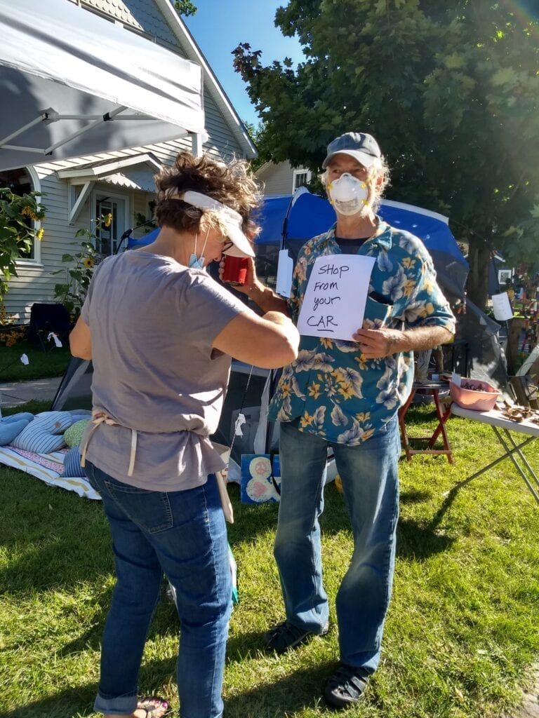 Laurie tapes a sign to Craig's chest during our successful yart sale last weekend.
