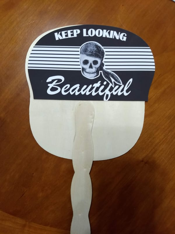 """the advertising side of the fan """"keep looking beautiful"""" with a pirate skull"""